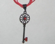 Bronze key with red rhinestone necklace on red organza ribbon