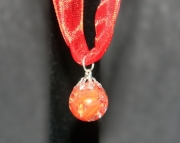 Orange cat eye stone on red organza ribbon
