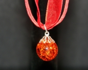 Orange stone on red organza ribbon